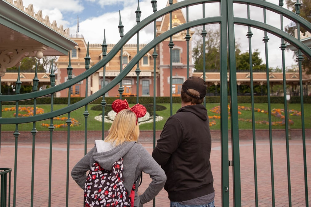 Disney tourists look through the fence after Disneyland was closed due to Coronavirus.